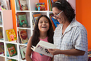 Kamilli Dias Vieira (left) laughing as she listens to a story with Neusa (right) in the community library, Biblioteca Comunitaria do Arquipelago, Porte Alegre, Brazil. <br /> <br /> Cirandar is working in partnership with  C&A and C&A Instituto to implement a network of Community Libraries in eight communities of Porto Alegre.