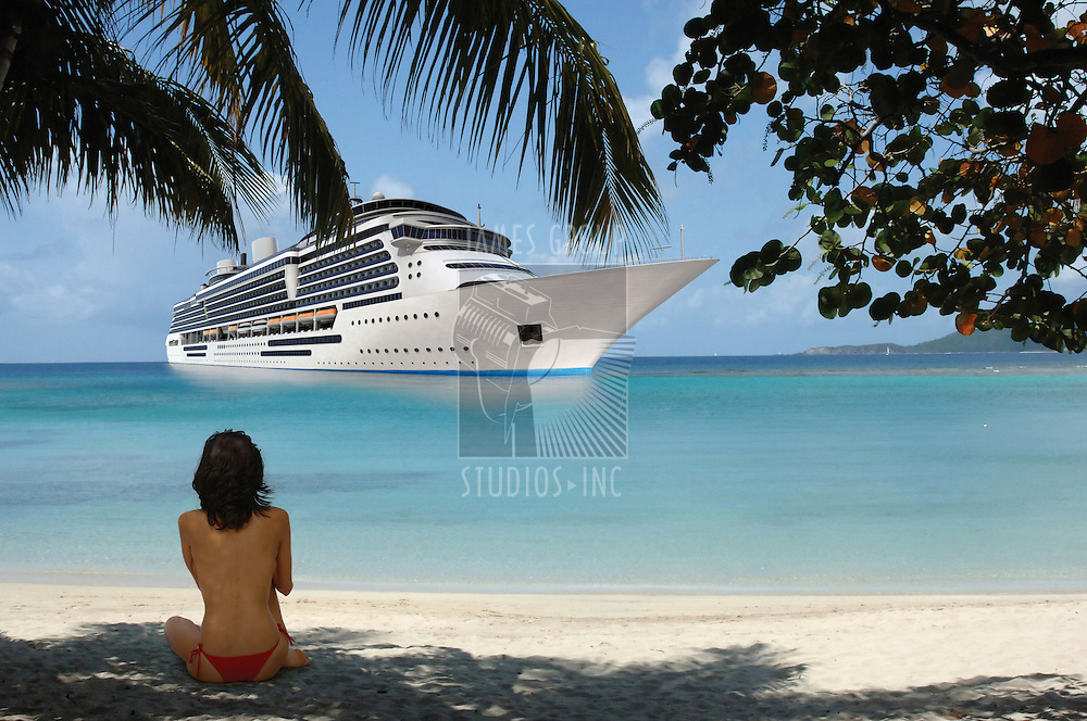 Young woman sitting on a tropical beach beneath the shade of palm fronds while facing the ocean where a cruise ship is moored in the distance
