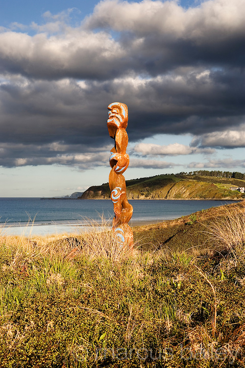 maori carving stands dignified in the dunes, looking over the new zealand coast at omaha, rodney district, new zealand