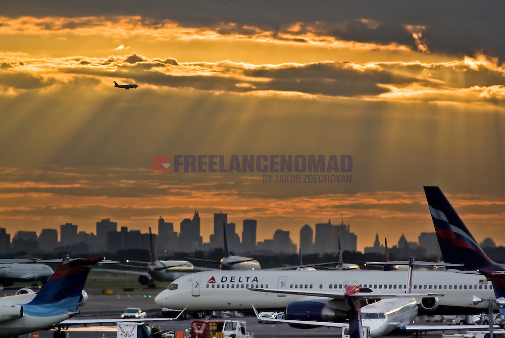 Evening rush hour at JFK New York Airport with landing plane through clouds and sunny spells and manhattan skyline delta airliners tarmac delay