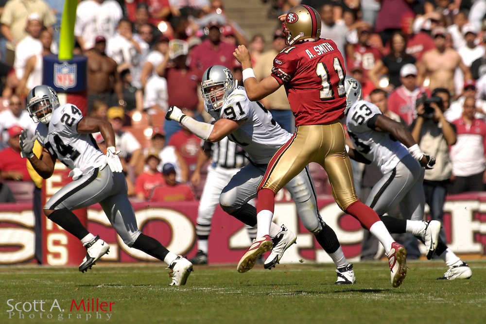 Oct. 8, 2006; San Francisco, CA, USA; Oakland Raiders defender (24) Michael Huff - (91) Tyler Brayton - (53) Thomas Howard follow San Francisco 49ers quarterback (11) Alex Smith as he throws the ball down field during their game at Monster Park. ....©2006 Scott A. Miller