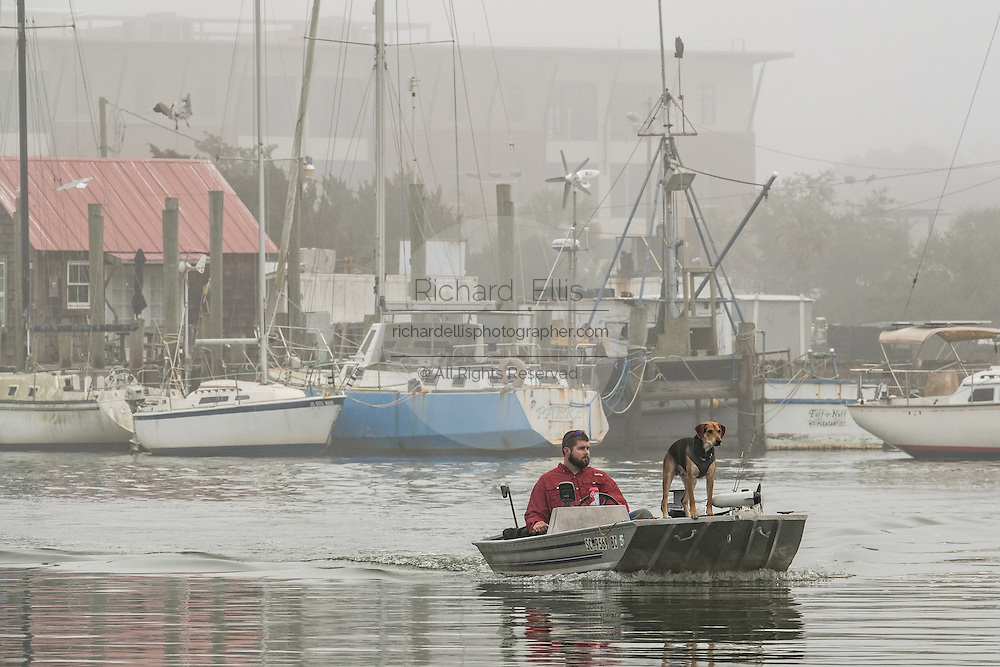 A fishermen heads out on Shem Creek with his dog in the bow during a foggy winter morning in Charleston, South Carolina.