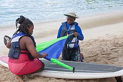 Alana Adams, left,  and Kaniel Richardson practice assembling a Taloo-ard paddlesail.  Practicing for Paddle in the Park at Magen's Bay. St. Thomas, USVI.  24 October 2015. © Aisha-Zakiya Boyd
