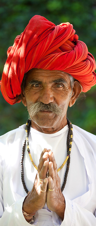 Traditional Namaste greeting from Indian man with traditional Rajasthani turban in village in Rajasthan, India. MODEL RELEASED.