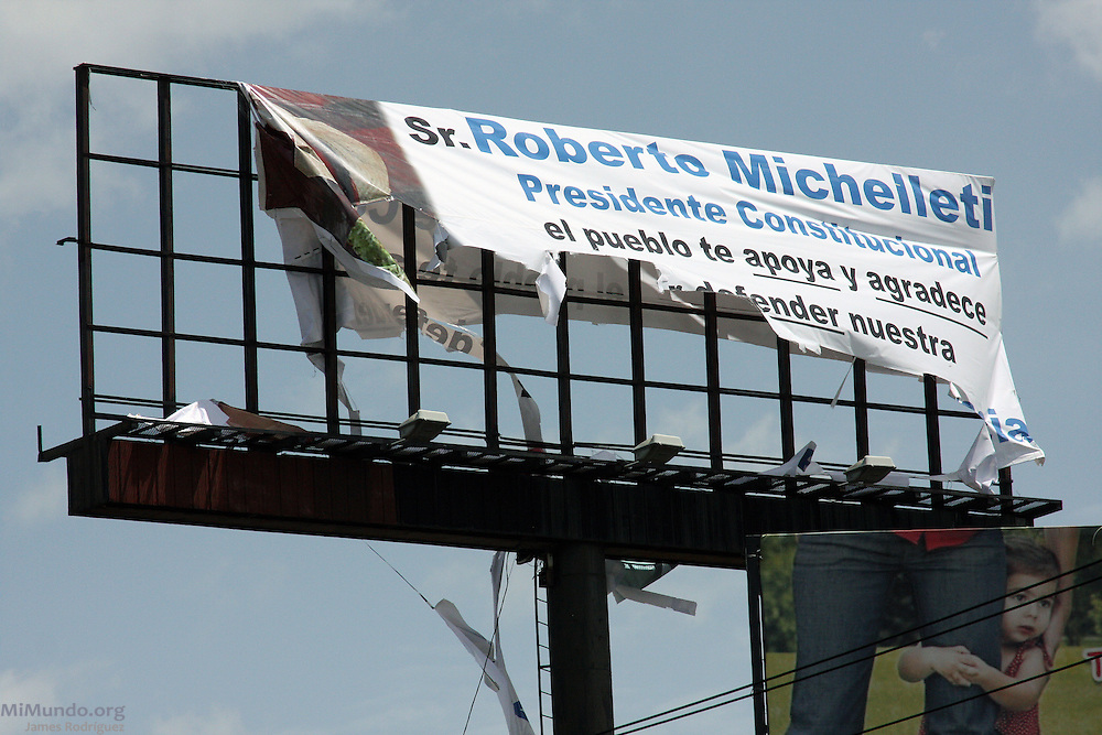 """Tegucigalpa, Honduras. July 4th, 2009. Protesters destroy a billboard in downtown Tegucigalpa that reads: """"Mr. Roberto Michelleti, Constitutional President, the people thank you and support you for defending our Constitution and Democracty."""" Mr. Michelleti occupied the position of de facto ruler after a Coup d'Etat forcibly removed President Manuel """"Mel"""" Zelaya on June 28th, 2009."""