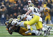 November 05, 2011: Iowa Hawkeyes running back Marcus Coker (34) is hit by Michigan Wolverines defensive back Blake Countess (18) and Michigan Wolverines cornerback Troy Woolfolk (29) during the first quarter of the NCAA football game between the Michigan Wolverines and the Iowa Hawkeyes at Kinnick Stadium in Iowa City, Iowa on Saturday, November 5, 2011. Iowa defeated Michigan 24-16.