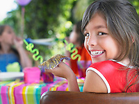 Portrait of young girl (10-12) at birthday party looking over shoulder