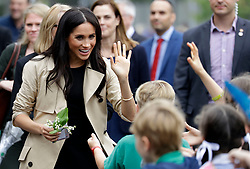 The Duchess of Sussex waves at children during a visit to Albert Park Primary School in Melbourne, on the third day of the royal couple's visit to Australia.