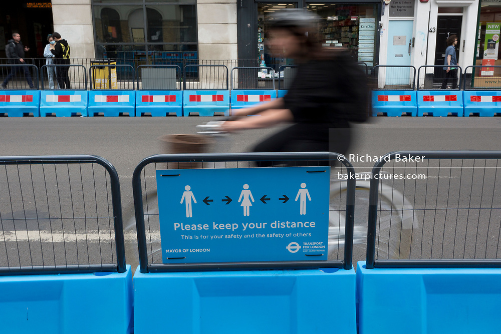 As the UK's Conornavirus pandemic lockdown continues, but with travel restrictions and social distancing rules starting to ease after three months of closures and isolation, a cyclist blurs past a social distance road sign where the road has been narrowed in favour of wider pedestrian pavements at Borough, on 9th June 2020, in London, England.