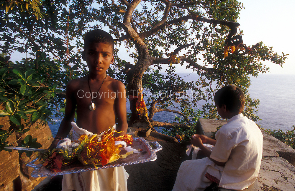 Sri Lanka..Young temple hands collect offerrings off a tree at Swami Rock. In Fort Frederick, this point is also called Lovers Leap. Site of a Hindu Kovil (temple) that overlooks Trincomalee Harbour.