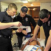 3/14/12 -- BATH, Maine.  Firefighter and EMT Kevin Hinds, left, confers with team leader and Paramedic Toby Martin as EMT Mike Brochu performs CPR on an electronically enhanced mannequin as part of Human Patient Simulator Lab (HPSL) training at the Bath Firehouse as his teammates support him in efforts to resuscitate the simulated patient. .HPSL is a Maine State EMS mobile training unit housed in a refitted Recreational Vehicle which delivers professional trainers statewide to locations to teach caregivers the latest protocols in emergency care. The mannequins are responsive to many different kinds of care, giving real-time feedback using the same tools EMTs use on real patients in the field. Photo by Roger S. Duncan.