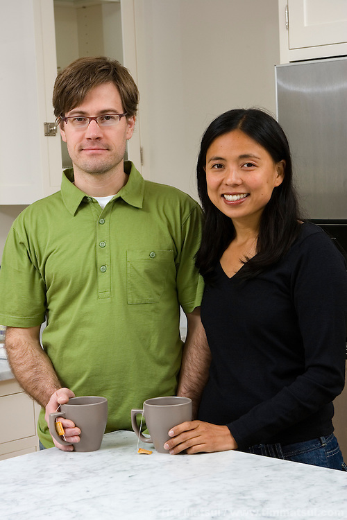 A asian woman and caucasian man in their kitchen at home.