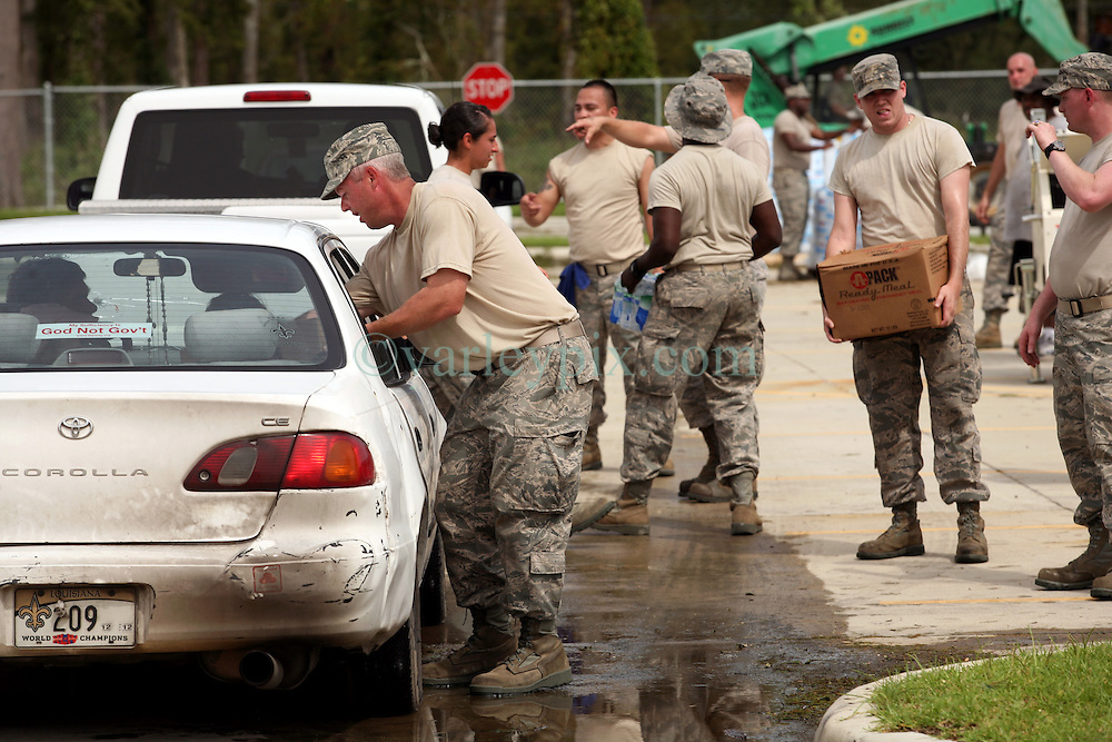 31st August 2012. St Bernard Parish, Louisiana,  USA. .Airmen from the Louisiana Air National Guard ensure that all their shirts are tucked in as they provide vital food, water and ice to the residents of areas battered by hurricane Isaac. There's a certain irony to the sign in the back window of the Corolla - 'God Not Govt' - especially seeing as who is doing the heavy lifting. Photo; Charlie Varley.