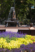 A view of the Archibald Fountain, Hyde Park , Sydney, Australia. The photo also shows colourful flowers and a young woman sitting on a park bench.