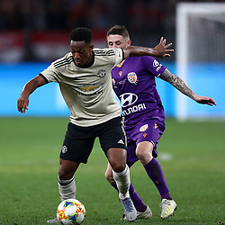 Anthony Martial of Manchester United holds off Jake Brimmer of Perth Glory