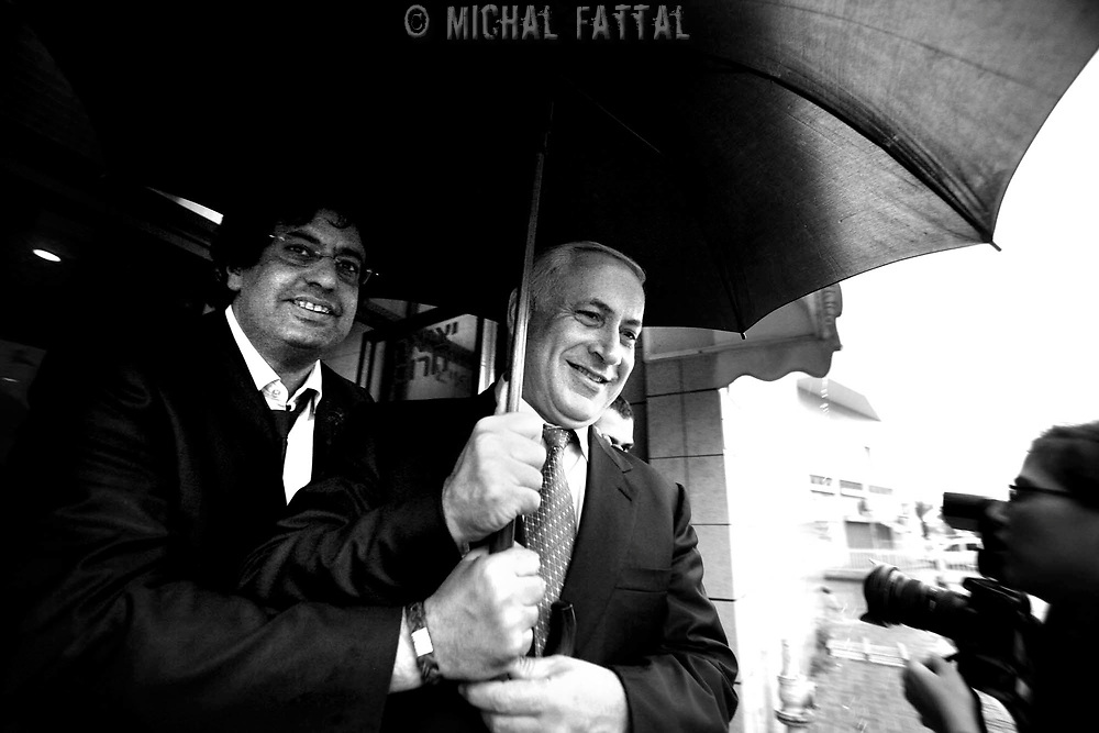 Benjamin Netanyahu runs out of a shopping center to escape the rain during an election campaign tour in southern Israel, February 2009.