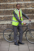 Happy young male engineer with bicycle against brick wall