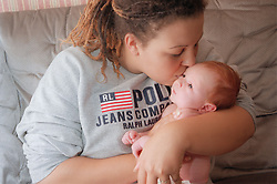 Mother holding and kissing newborn baby daughter,