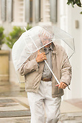 An elderly man tries to protect himself from blowing rain and wind as Hurricane Joaquin brings heavy rain, flooding and strong winds as it passes offshore October 3, 2015 in Charleston, South Carolina.