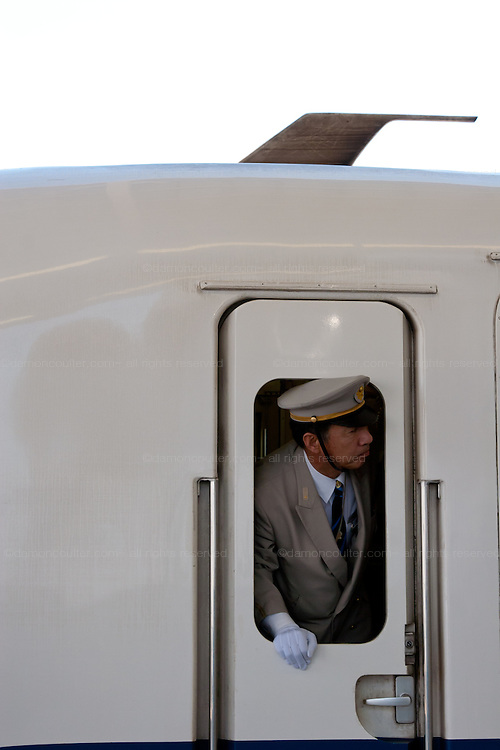 A guard looks out of the window of a JR 700 class Shinkansen bullet train at Shin-Yokohama station with the communication aerial visable on the train roof above him. Yokohama, Japan. August 14th 2008