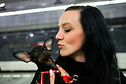 Young lady kissing her Chihuahua dog at the Muzeum subway station in Prague.