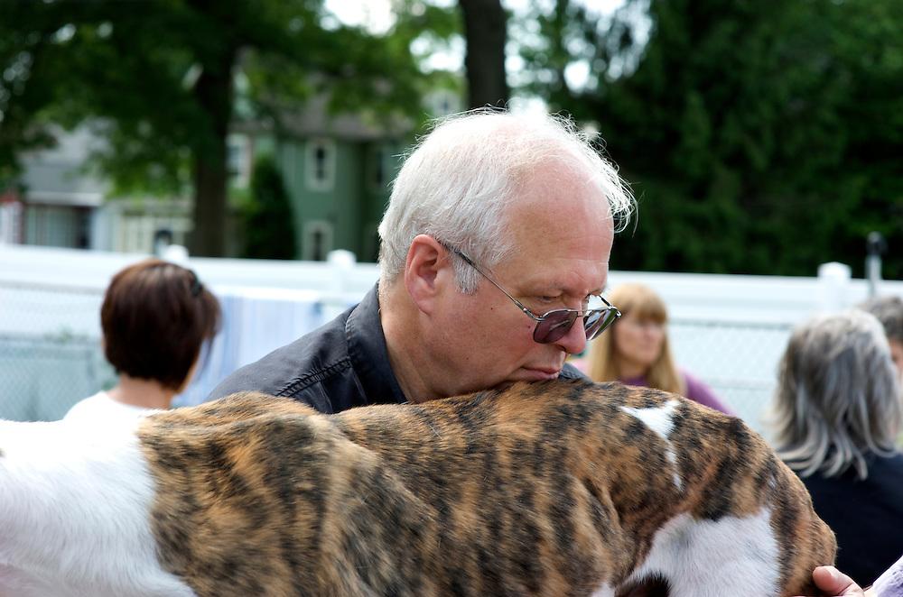 A New Jersey Greyhound Adoption Program (NJGAP) volunteer steadies a rescued retired greyhound racer, named Barack.