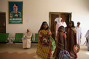 Beneath the imposing portrait of their Sudanese President in Al Fashir airport, Omar Hassan Ahmad al-Bashir, a Darfurian lady and children await the entourage of British peer Lord Ahmed of Rotheram who has brought over from the UK, a delegation to attend the first-ever international Conference on Womens' Challenge in Darfur, hosted by the govenor in his own compound.