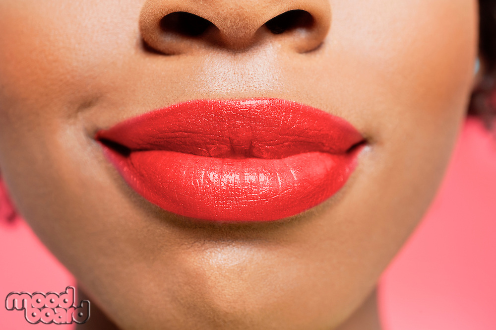 Close-up view of an African American woman's red lips over colored background