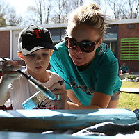 Mills Allgood, 5, and his mom Holly paint the wood for the garden at ECEC Saturday as a part of 10 for Tupelo's clean up effort