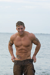 good looking muscular blonde man standing in water pulling up his pants