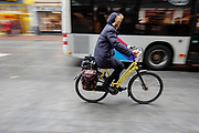 Een vrouw fietst door het centrum van Nijmegen terwijl ze wordt ingehaald door een stadsbus.<br /> <br /> A woman cycles in the city center of Nijmegen while being passed by a bus.