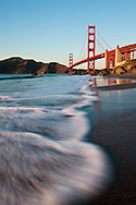 Surf washes over the beach with the Golden Gate Bridge in the background - San Francisco, California
