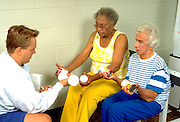 Trainer age 25 lifting weights with friends age 70 and age 80 at Lynnwood Recreation Center.  St Paul Minnesota USA