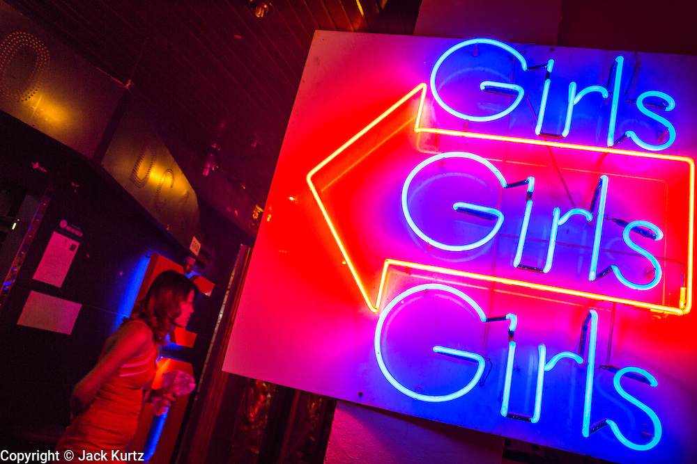 "19 JANUARY 2013 - BANGKOK, THAILAND:  A woman stands in the entrance to DC10, a ""go-go bar"" in the Nana Entertainment District in Bangkok. Prostitution in Thailand is technically illegal, although in practice it is tolerated and partly regulated. Prostitution is practiced openly throughout the country. The number of prostitutes is difficult to determine, estimates vary widely. Since the Vietnam War, Thailand has gained international notoriety among travelers from many countries as a sex tourism destination. One estimate published in 2003 placed the trade at US$ 4.3 billion per year or about three percent of the Thai economy. It has been suggested that at least 10% of tourist dollars may be spent on the sex trade. According to a 2001 report by the World Health Organisation: ""There are between 150,000 and 200,000 sex workers (in Thailand).""    PHOTO BY JACK KURTZ"