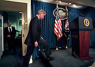 President Bill Clinton walks into the White House press briefing room to announce that America and NATO had began to bomb targets in Serbia, March 24, 1999. At left is Clinton's national security adviser Sandy Berger. (Photo by Roger M. Richards)