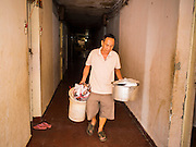 24 FEBRUARY 2015 - PHNOM PENH, CAMBODIA: A resident of the White Building takes his garbage out. The White Building, the first modern apartment building in Phnom Penh, originally had 468 apartments, and was opened the early 1960s. The project was overseen by Vann Molyvann, the first Cambodian architect educated in France. The building was abandoned during the Khmer Rouge occupation. After the Khmer Rouge were expelled from Phnom Penh in 1979, artists and dancers moved into the White Building. Now about 2,500 people, mostly urban and working poor, live in the building. Ownership of the building is in dispute. No single entity owns the building, some units are owned by their occupants, others units are owned by companies who lease out apartments. Many of the original apartments have been subdivided since the building opened and serve as homes to two or three families. The building has not been renovated since the early 1970s and is in disrepair. Phnom Penh officials have tried to evict the tenants and demolish the building but residents refuse to move out.   PHOTO BY JACK KURTZ