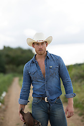 cowboy holding a saddle and standing on a dirt road