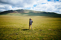 A young woman walks into the vast open plains of northern Mongolia.