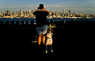 USA. New York -young man with dog watching Manhattan skyline with a binocular, from port imperial park in New Jersey   /  jeune homme avec son chien regardant a la jumelle le skyline de Manhattan depuis le Parc de Port Imperial  a New Jersey