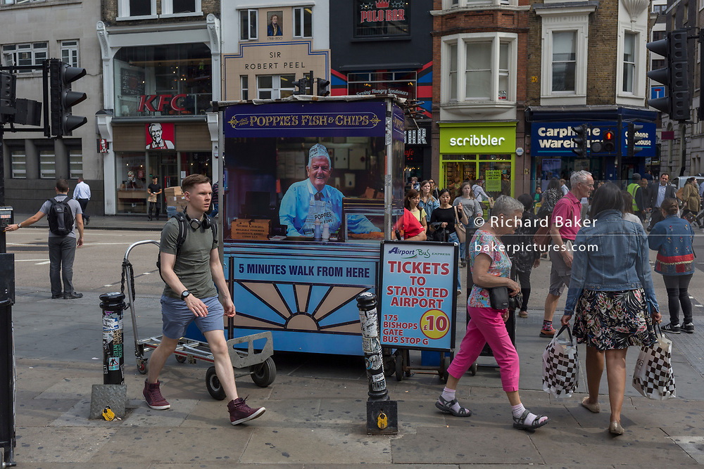 Pedestrians and passers-by and the rear of a newspaper vendor's kiosk outside Liverpool Street mainline station in the City of London - the capital's financial district, on 3rd September 2018, in London England.