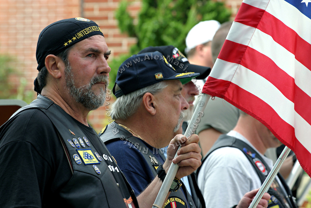 Members of the Patriot Guard Riders holding US flags during the funeral service of Sgt. Ian T. Sanchez, in Staten Island, NY., on Tuesday, June 27, 2006. Sgt. Sanchez, a 26-year-old American serviceman was killed by a roadside bomb in the Pech River Valley, Afghanistan. The Patriot Guard Riders is a diverse amalgamation of riders from across the United States of America. Besides a passion for motorcycling, they all have in common an unwavering respect for those who risk their lives for the country's freedom and security. They are an American patriotic group, mainly but not only, composed by veterans from all over the United States. They work in unison, calling upon tens of different motorcycle groups, connected by an internet-based web where each of them can find out where and when a 'Mission' is called upon, and have the chance to take part. This way, the Patriot Guard Riders can cover the whole of the United States without having to ride from town to town but, by organising into different State Groups, each with its own State Captain, they are still able to maintain strictly firm guidelines, and to honour the same basic principles that moves the group from the its inception. The main aim of the Patriot Guard Riders is to attend the funeral services of fallen American servicemen, defined as 'Heroes' by the group,  as invited guests of the family. These so-called 'Missions' they undertake have two basic objectives in particular: to show their sincere respect for the US 'Fallen Heroes', their families, and their communities, and to shield the mourners from interruptions created by any group of protestors. Additionally the Patriot Guard Riders provide support to the veteran community and their families, in collaboration with the other veteran service organizations already working in the field.   **ITALY OUT**