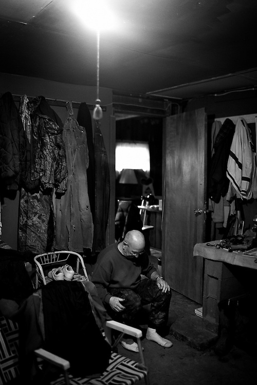 Dave Bircher, 71, sits down to take off his boots and rest in the garage after a long day of chores on the farm. Bircher has farmed the rolling hills of Southeast Ohio for more than thirty years. 'Honestly, we're farming because we love to farm. We're not farming because we're making any money,' says Bircher.