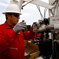 A worker holds up a sample bottles with water and oil separated from running oil through the Ocean Therapy Solutions oil separating centrifuge device during a demonstration on a vessel at Hornbeck Offshore in Port Fourchon, Louisiana, U.S., on Tuesday, June 15, 2010. (Mandatory Credit: Derick E. Hingle)