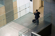 businessman talking on his cellphone on a hallway bridge of a large office building