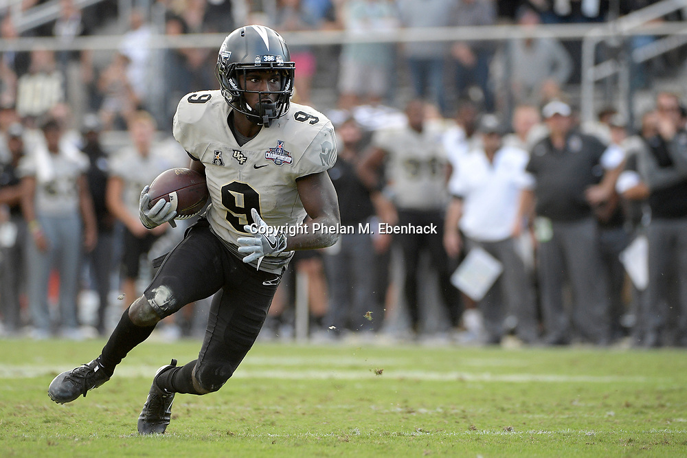 Central Florida running back Adrian Killins Jr. (9) rushes for yardage during the second half of the American Athletic Conference championship NCAA college football game against Memphis Saturday, Dec. 2, 2017, in Orlando, Fla. Central Florida won 62-55. (Photo by Phelan M. Ebenhack)