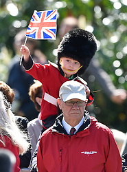 © Licensed to London News Pictures. 20/04/2016. HRH A young boy dressed in a bearskin and military uniform waves the union flag as he watches Queen Elizabeth II officially open the new bandstand at Alexandra Gardens in Windosr on the eve of her 90th birthday. Photo credit: Hannah McKay/LNP