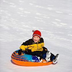 A young boy (age 4) rides his snow tube down a  hill in Quechee, Vermont.
