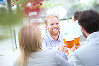 Happy businessman toasting beer glass with colleagues at outdoor restaurant