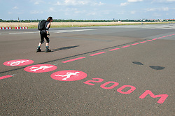 Woman inline skating on runway at new city public Tempelhofer Park on site of famous former Tempelhof Airport in Berlin Germany