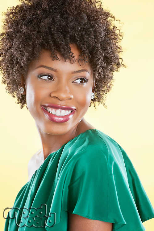 Attractive African American woman in an off shoulder dress looking away over colored background